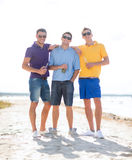 Friends on the beach with bottles of drink Royalty Free Stock Image