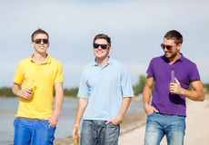 Friends on the beach with bottles of drink Royalty Free Stock Photography