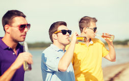 Friends on the beach with bottles of drink Royalty Free Stock Photos