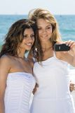 Friends on beach having fun. Two beautiful friends on beach taking selfportrait with a cellphone camera Stock Photography