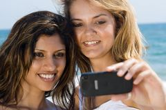 Friends on beach having fun. Two beautiful friends on beach taking selfportrait with a cellphone camera Stock Images