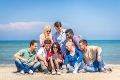 Friends on the beach looking tablet. Group of friend looking a tablet on the beach royalty free stock image