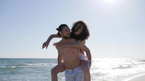 Friends at beach, merry girl jumping on guy`s back in backlight, love couple on vacation, wind develops women hair. Ocean coast, background beautiful beach stock footage