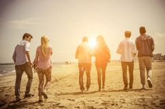 Friends on the beach. Multi-ethnic group of friends walking on the beach and talking - Group of young adults silhouettes at sunset Royalty Free Stock Photography