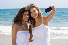 Friends on beach taking photo. Two beautiful friends on beach taking selfportrait with a cellphone camera Royalty Free Stock Image