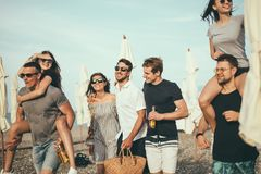 Group of Friends Walking at Beach, having fun, womans piggyback on mans, funny vacation. Friends on beach walking, having fun, dancing, couples hugging stock photography