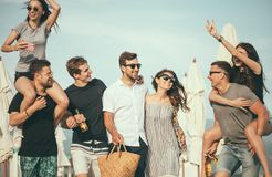 Group of Friends Walking at Beach, having fun, womans piggyback on mans, funny vacation. Friends on beach walking, having fun, dancing, couples hugging royalty free stock image
