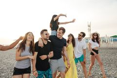 Group of Friends Walking at Beach, having fun, womans piggyback on mans, funny vacation. Friends on beach walking, having fun, dancing, couples hugging royalty free stock photos