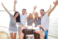 Friends on beach waving hands and photographing Royalty Free Stock Image