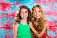Friends beautiful children girls hug together happy smiling. On grunge background Stock Photos