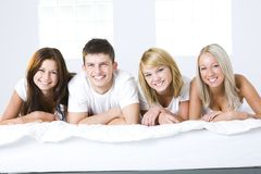 Friends in bed. Happy friends lying in bed and looking at camera. Front view Royalty Free Stock Photos