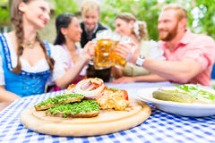 Friends in beer garden with drink and Bavarian appetizers Royalty Free Stock Photography