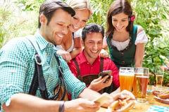 Friends in beer garden looking at Stock Image