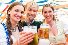 Friends with beer glasses at Bavarian beer tent royalty free stock photos