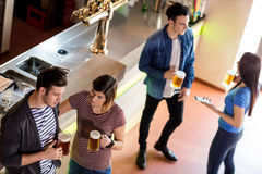 Friends with beer mug by counter in bar stock photography