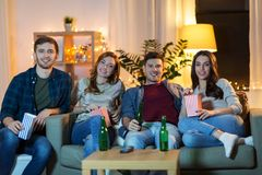Friends with beer and popcorn watching tv at home royalty free stock photos