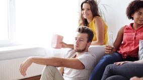 Friends with beer talking and watching tv at home. Friendship, leisure, people and entertainment concept - bored man and friends drinking beer or cider, talking stock video footage
