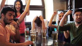 Friends with beer watching football at bar or pub stock video footage