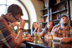 Friends with beer watching football at bar or pub Royalty Free Stock Images