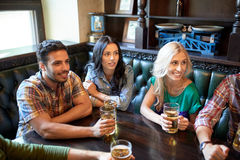 Friends with beer watching football at bar or pub Royalty Free Stock Photo