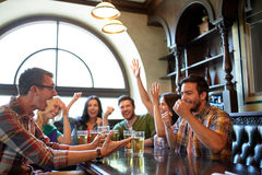 Friends with beer watching football at bar or pub. People, leisure, friendship and entertainment concept - happy friends drinking beer, watching sport game or Royalty Free Stock Image