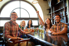 Friends with beer watching football at bar or pub. People, leisure, friendship and entertainment concept - happy friends drinking beer, watching sport game or Stock Photos