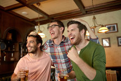 Friends with beer watching sport at bar or pub Royalty Free Stock Photos