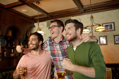 Friends with beer watching sport at bar or pub Stock Image