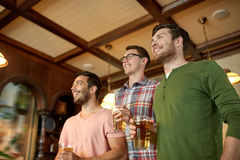 Friends with beer watching sport at bar or pub Royalty Free Stock Photography