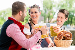 Friends in beergarden clinking glasses with beer. Friends in beer garden clinking glasses with beer, pretzel standing on the table Royalty Free Stock Photography