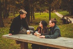Friends behind wooden table in autumn park Stock Images