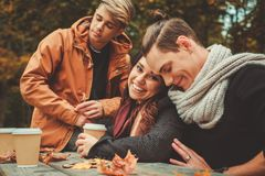 Friends behind wooden table in autumn park Stock Image