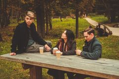 Friends behind wooden table in autumn park Royalty Free Stock Photos