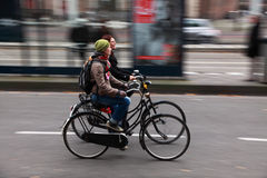 Friends on bicycles. Amsterdam,Netherlands- October 30th, 2011:Panning image of a two young women riding their bicycles in a street in Amsterdam. Amsterdam is Stock Image