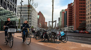 Friends on Bicycles. Rotterdam, The Netherlands- April 24, 2012: Image of two image of a two happy young women riding their bicycles in a street in Rotterdam Royalty Free Stock Image