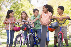 Friends with bicycles scooters and skateboard Royalty Free Stock Image
