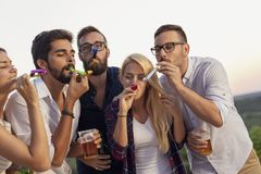 Friends blowing party whistles royalty free stock photo