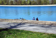 Friends by blue water after riding bicycles. Two man sitting and relaxing by lake Stock Photos