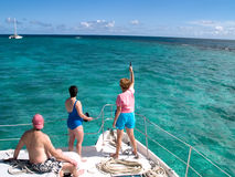 Friends Boating In Tropical Water. Three friends on the bow of a boat watching a sailboat in the Caribbean Ocean Stock Images
