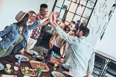 Friends bonding. Top view of young people giving each other high-five in a symbol of unity and smiling while having a dinner party indoors royalty free stock images