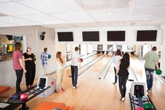 Friends Bowling in Club. Group of young friends bowling in club stock image