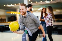 Friends bowling at club. And having fun playing casually stock images