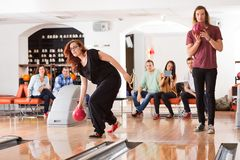 Friends Bowling in Club Stock Image