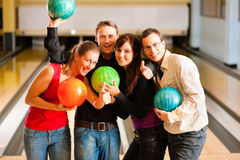 Friends bowling together Royalty Free Stock Photos