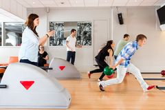 Friends Bowling Together in Club Stock Image