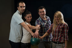 Friends Bowling Together. Group Of Four Friends In A Bowling Alley Having Fun. Holding Their Bowling Balls And Showing Thumbs Up stock photo