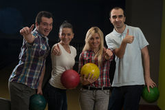 Friends Bowling Together. Group Of Four Friends In A Bowling Alley Having Fun. Holding Their Bowling Balls And Showing Thumbs Up royalty free stock image