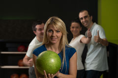 Friends Bowling Together. Group Of Four Friends In A Bowling Alley Having Fun, Three Of Them Cheering The One In Charge To Throw The Bowling Ball stock photography