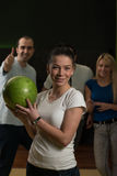 Friends Bowling Together. Group Of Four Friends In A Bowling Alley Having Fun, Three Of Them Cheering The One In Charge To Throw The Bowling Ball stock photo