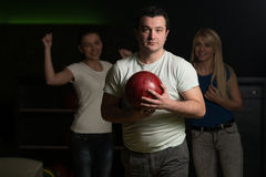 Friends Bowling Together. Group Of Four Friends In A Bowling Alley Having Fun, Three Of Them Cheering The One In Charge To Throw The Bowling Ball stock images